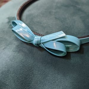 Plastic headband with blue faux leather bow